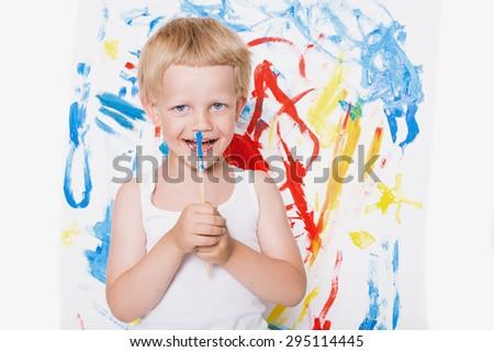 Artist preschool boy painting brush watercolors on a easel. School. Education. Creativity. Studio portrait over white background - stock photo