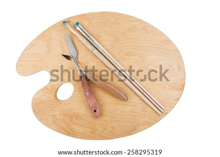 Artist's clean palette with brush and palette knife isolated over white background. - stock photo