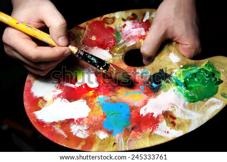 Artist�¢??s hand holding a paintbrush and art palette - stock photo