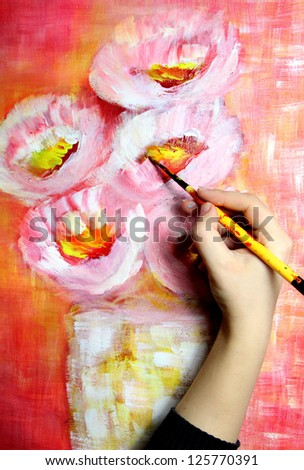 Artist�¢??s hand holding a paintbrush and paints beautiful picture - stock photo
