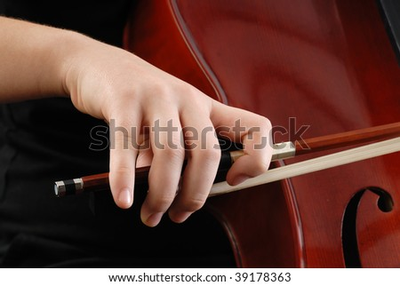 artist's hand holding fiddle stick while playing cello on concert