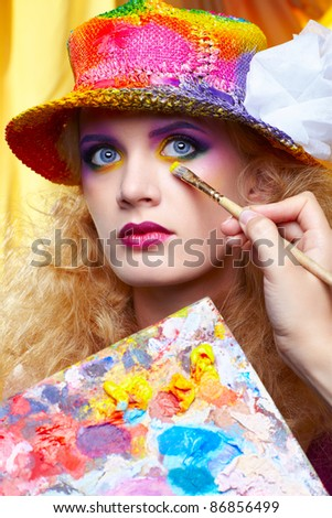 artist's hand with paintbrush painting beautiful girl's colorful eye shadow make up using palette - stock photo