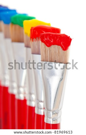 Artist's paintbrushes holding all seven colors of the rainbow - red, orange, yellow, green, blue, indigo and violet - stock photo
