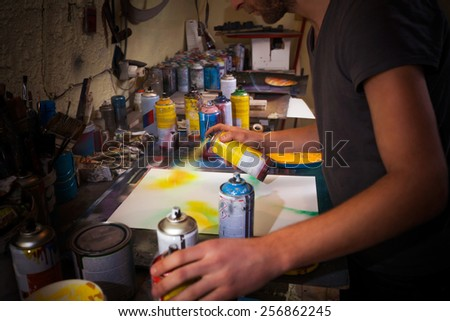 Artist's working in his studio. Painter's creating new image using spray paints. - stock photo