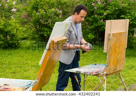 Artist Standing By His Sketchbook And Preparing To Work On The Painting In The Garden - stock photo