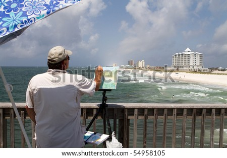 Artist uses a small brush to paint on canvas the view of the shoreline from a pier on Pensacola Beach, Florida. - stock photo