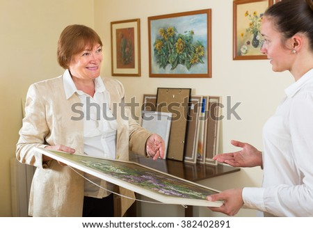 Artist with buyer the picture in art gallery - stock photo