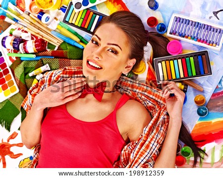 Artist woman lying on paint palette. - stock photo