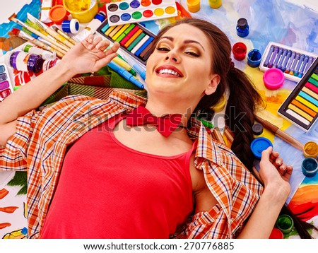 Artist woman lying on paint palette. Red t-shirt. - stock photo