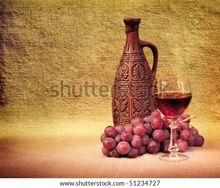 Artistic arrangement of bottles of wine, glass and grapes - stock photo