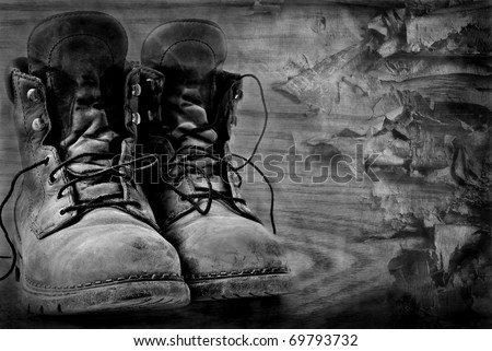 Artistic black and white image of rugged  boots on wood textured background. - stock photo
