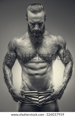 Artistic black and white picture of muscular tattooed man with beard. - stock photo