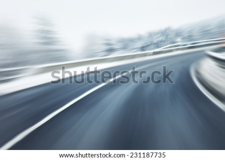 Artistic blurry dangerous fast driving at the icy snow road. Motion blur visualizies the speed and dynamics. - stock photo
