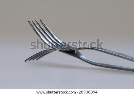 Artistic closeup of two forks mirroring each other - stock photo