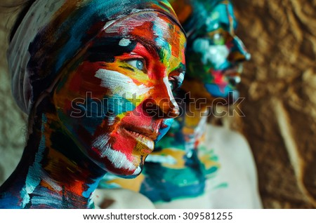 Artistic colorful portrait of a young beautiful model with big blue eyes and creatively painted face - stock photo