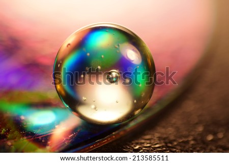 Artistic composition of colorful marble glass ball on wet CD - stock photo