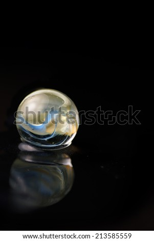Artistic composition of marble glass ball on water, black background
