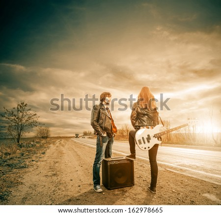 artistic couple with guitar on a freeway sunset - stock photo