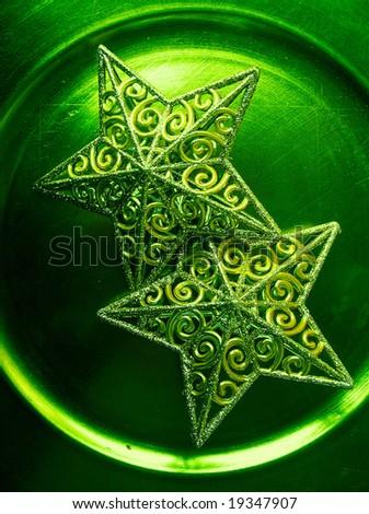 artistic cross process macro shot of two filigree christmas stars against a reflecting metallic background - stock photo