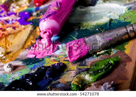 Artistic equipment: paint, brushes and knives on paint background - stock photo