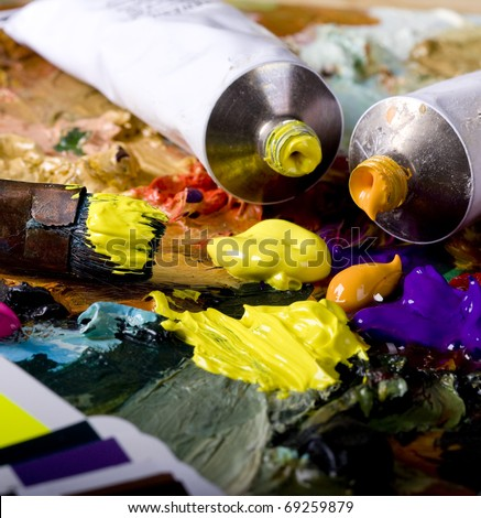 Artistic equipment: paint, brushes and knives on paint background