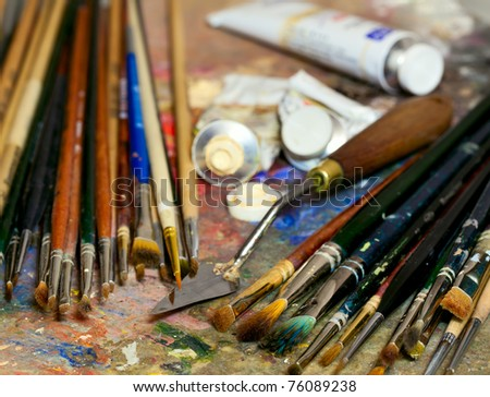 Artistic equipment: paint, brushes, spatula and art palette. Shallow depth of field - stock photo