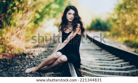 Artistic fashion portrait of young brunette sitting on railroad. Shallow depth of field