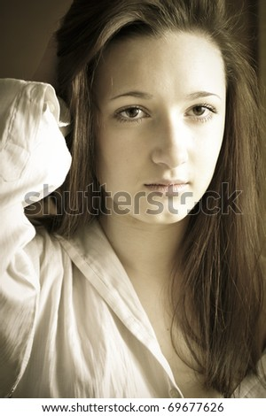 Artistic fashion portrait of young pretty woman near the window at her apartment early in the morning with natural light - stock photo