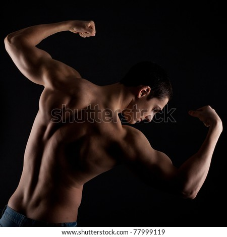 Artistic Fitness on a black background, Low key portrait of young bodybuilder posing and showing muscles - stock photo
