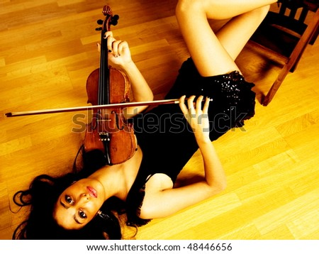 Artistic image of a lovely female violinist playing her instrument - stock photo