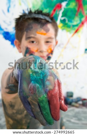 Artistic little boy holding out his paint covered hand to the camera as he stands in front of his modern abstract painting - stock photo