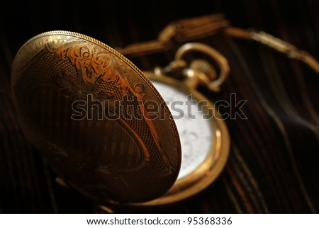 Artistic low key image of antique pocket watch on striped velvet fabric.  Macro with extremely shallow dof. - stock photo