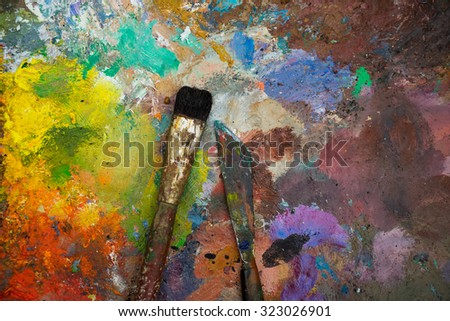Artistic paintbrushes and palette knifes on an old wooden  palette - stock photo
