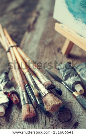 Artistic paintbrushes, tubes of oil paint, palette knife and easel with oil painting on old wooden desk. - stock photo