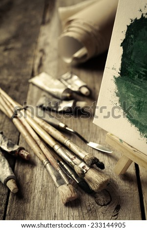Artistic paintbrushes, tubes of oil paint, palette knife and easel with oil painting on old wooden desk. Vintage stylized photo. - stock photo
