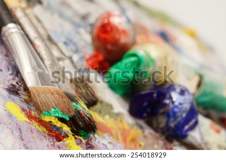 Artistic palette with colourful oil paints, dirty brushes - background for creative art design - stock photo