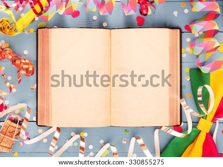Artistic party card or invitation background with a colorful frame of spiral streamers, confetti, a champagne cork and bow tie around an open book with double spread blank pages for your text - stock photo