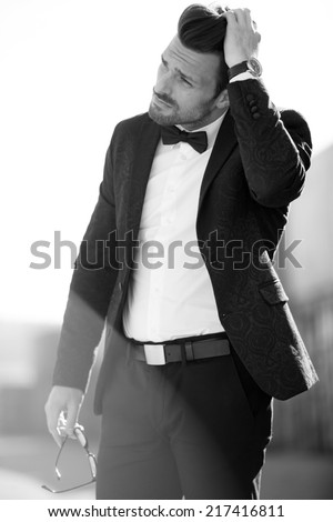 Artistic photo of a man in suit with natural lit dust particles in air, with bow tie - stock photo