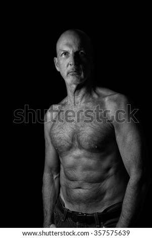 Artistic photo of a muscular, athletic man in his sixties isolated on a black background