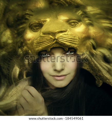 Artistic portrait of a beautiful young woman with a mask of the face of a majestic golden lion