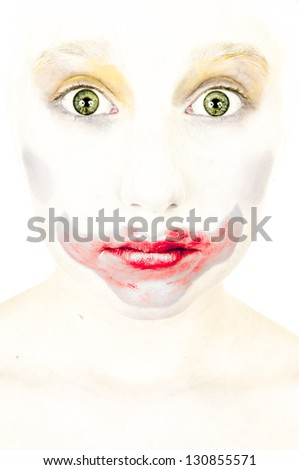 artistic portrait of a little girl with face painted as a clown amazed