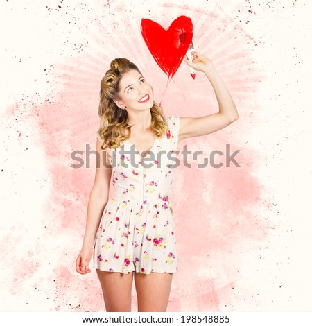 Artistic portrait of a retro fifties blond pin-up girl painting red love heart symbol during valentines day. Romance in art - stock photo