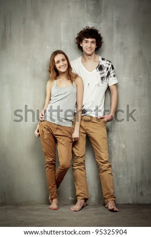 Artistic portrait of a young couple on a gray, textural background. - stock photo