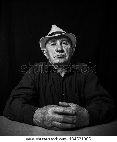 Artistic portrait of an old man in a hat - stock photo