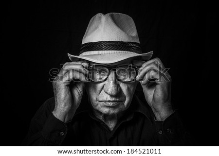 Artistic portrait of an old man with glasses and hat - stock photo