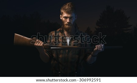 Artistic portrait of angry mid aged man holding shotgun in his hands. Dramatic concept - stock photo