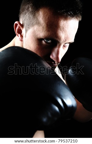 Artistic portrait of attractive boxer against black background - stock photo