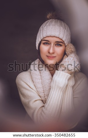 Artistic portrait of brunette woman in winter hat and fur gloves.