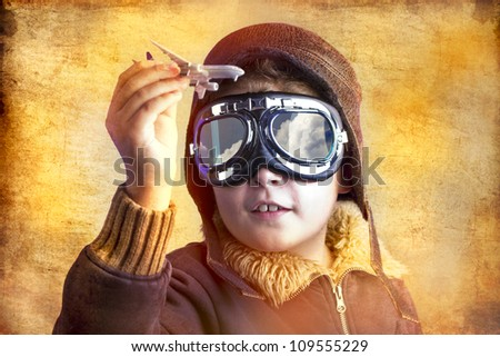 artistic portrait of child with former flight suit, with hat and sunglasses - stock photo