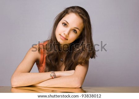 Artistic portrait of confident young brunette with golden reflection hue. - stock photo